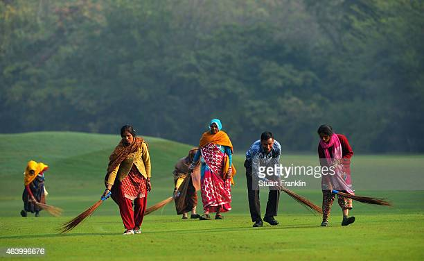 Workers wearing traditional indian dress sweep the fairway prior to the third round of the Hero India Open Golf at Delhi Golf Club on February 21,...