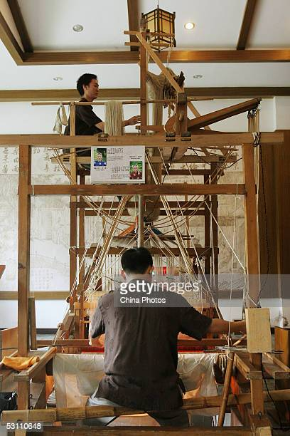 Workers weave Shu Brocade with old traditional looms at a Shu Brocade factory on June 21 2005 in Chengdu of Sichuan Province China Shu Brocade also...