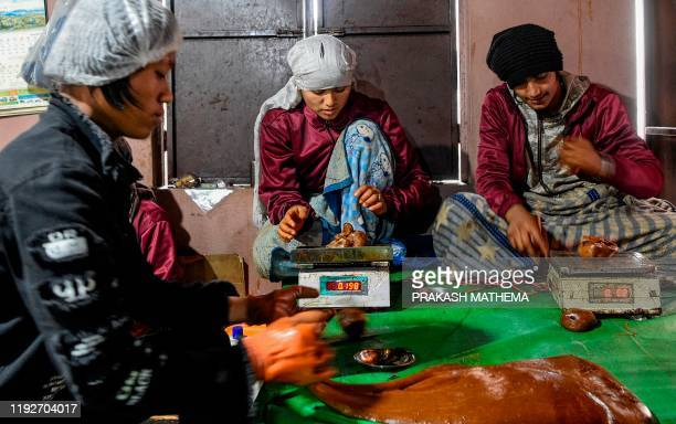 Workers weigh molten raw hardened molasses locally know as Chaku for the upcoming Maghe Sankranti festival in Tokha on the outskirts of Kathmandu on...