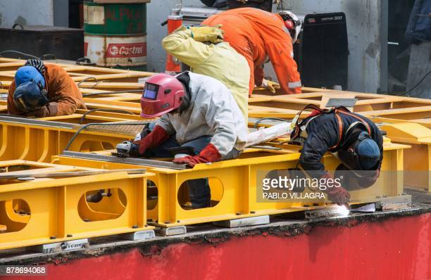 Workers weld the deck of the Sophie Siem vessel where members of the US Navy Undersea Rescue Command will install the US Navy Pressurized Rescue...
