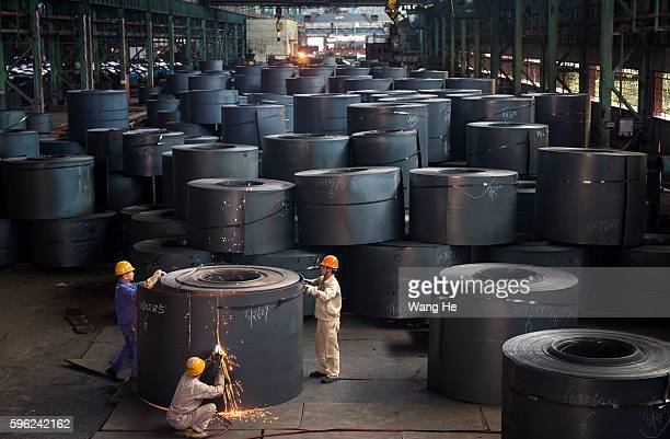 Workers weld the ends of hot rolled steel on the line at the Wuhan Iron Steel Group Corp on August 27 in Wuhan China The two of China's biggest steel...