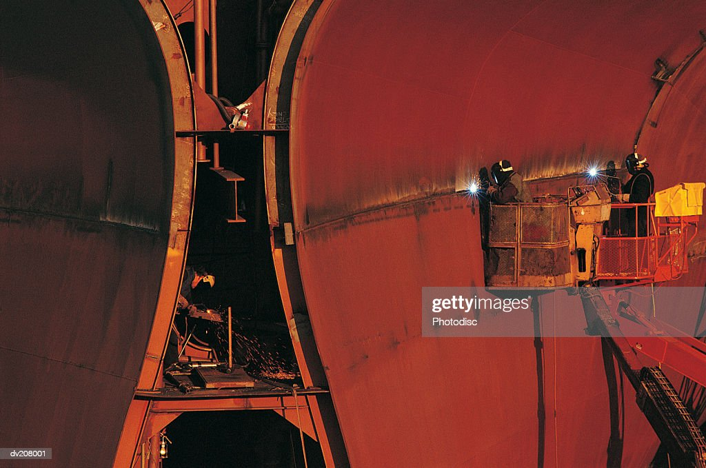 Workers welding a ship's hull : Stock Photo