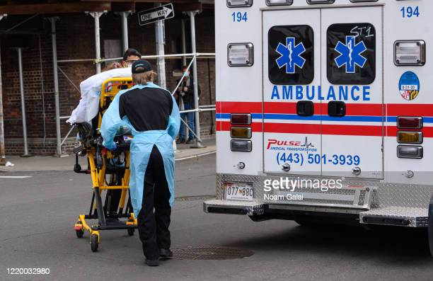 EMS workers wheel a patient outside Elmhurst Hospital Center during the coronavirus pandemic on April 20 2020 in New York City COVID19 has spread to...