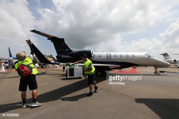 Workers wipe a wing of an Embraer SA Phenom 300 aircraft during a media preview day at the Singapore Airshow held at the Changi Exhibition Centre in...