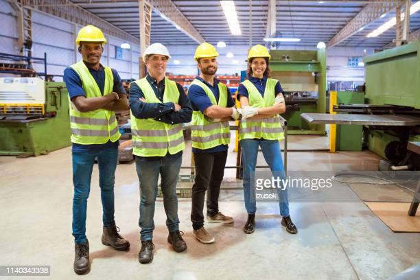 workers with arms crossed standing in factory - izusek stock pictures, royalty-free photos & images