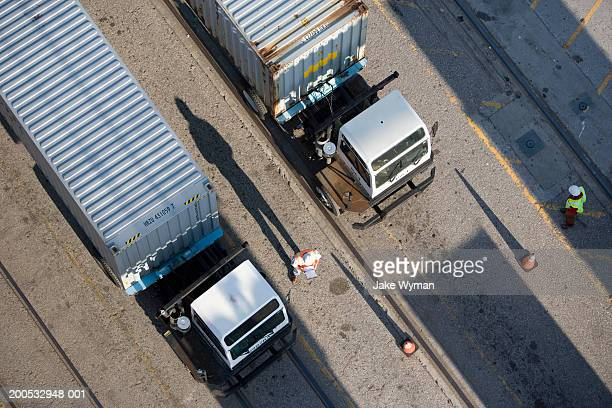 Workers with articulated lorry on docks, overhead view
