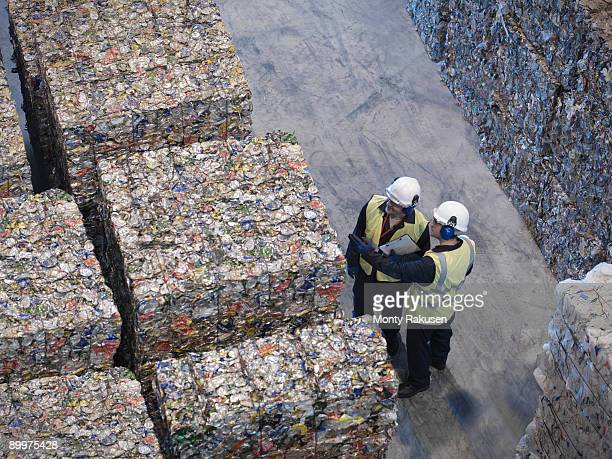 workers with bales of tin cans - environmental damage stock pictures, royalty-free photos & images