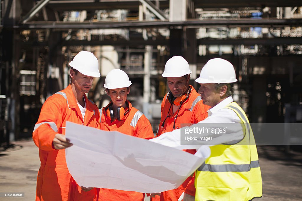 Workers with blueprints at oil refinery : Stock Photo