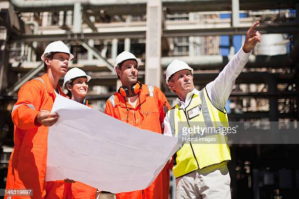 Workers with blueprints at oil refinery