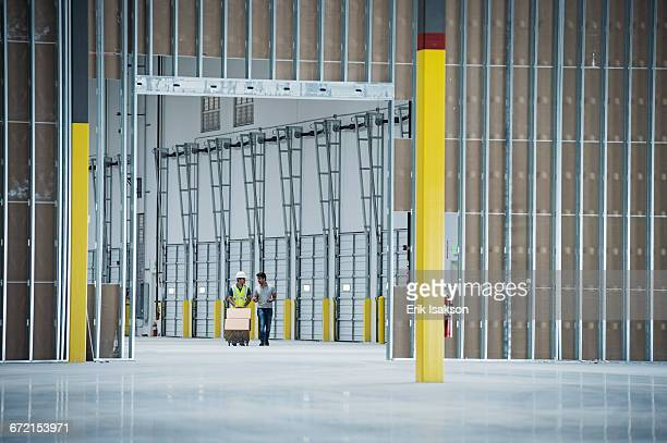 Workers with boxes on hand truck in empty warehouse