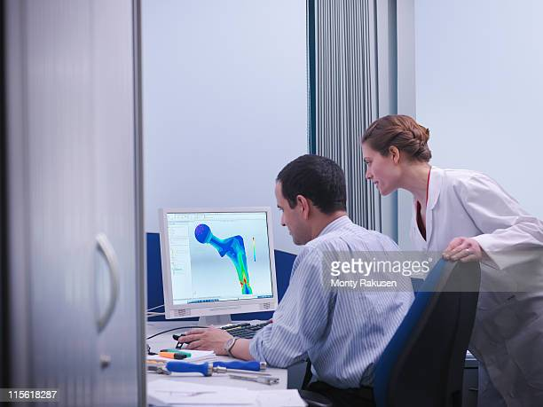 Workers with CAD drawing in office