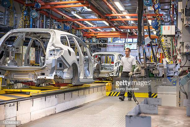 Workers with car bodies on production line in car factory