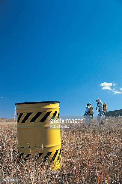 Workers with chemical waste drum
