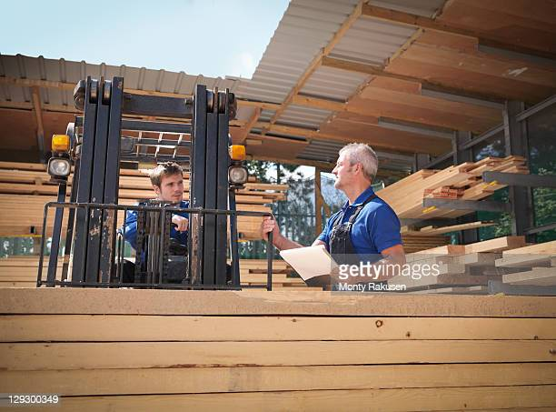 Workers with clipboard and fork lift in wood store of joinery
