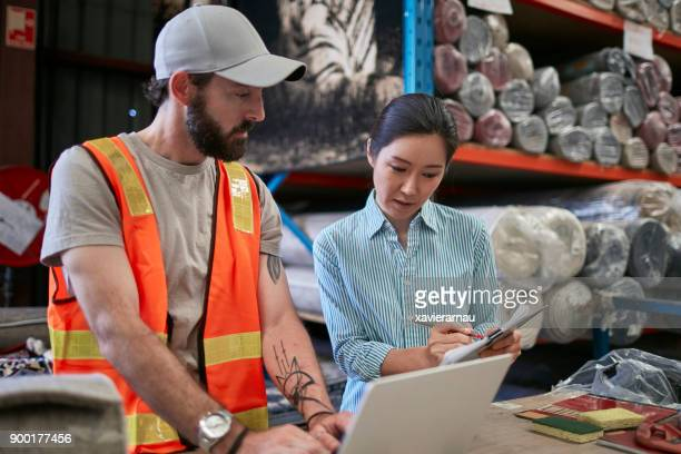 Workers with clipboard and laptop in rug warehouse
