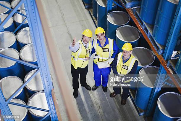 workers with clipboards in warehouse - stahlfass stock-fotos und bilder