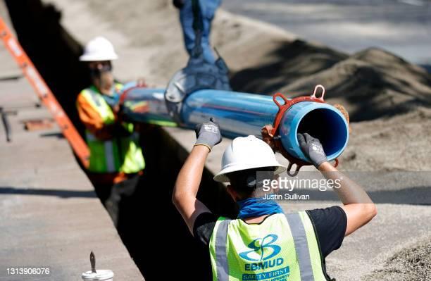 Workers with East Bay Municipal Utility District install new water pipe on April 22, 2021 in Walnut Creek, California. U.S. President Joe Biden...