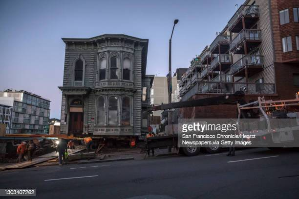 Workers with Phil Joy House Movers and Scott House Movers finish the final preparations before the two-story Victorian home is relocated from 807...