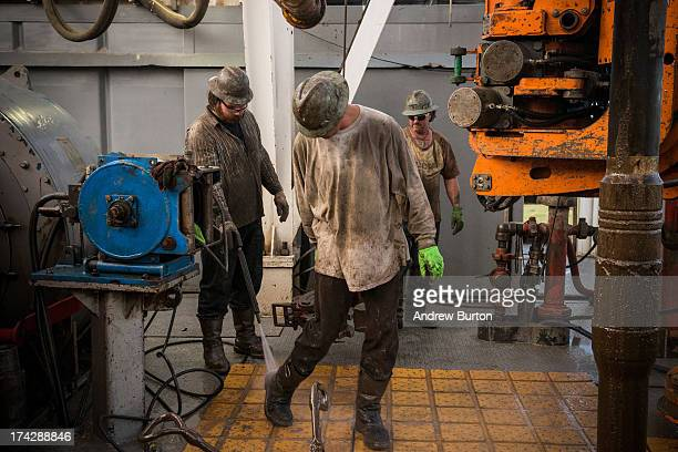 Workers with Raven Drilling clean themselves off while drilling for oil in the Bakken shale formation on July 23 2013 outside Watford City North...