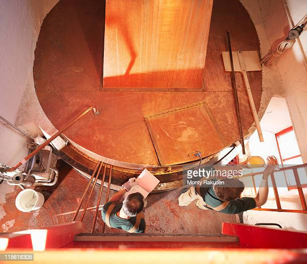 workers with sample at copper tank - storage tank stock pictures, royalty-free photos & images