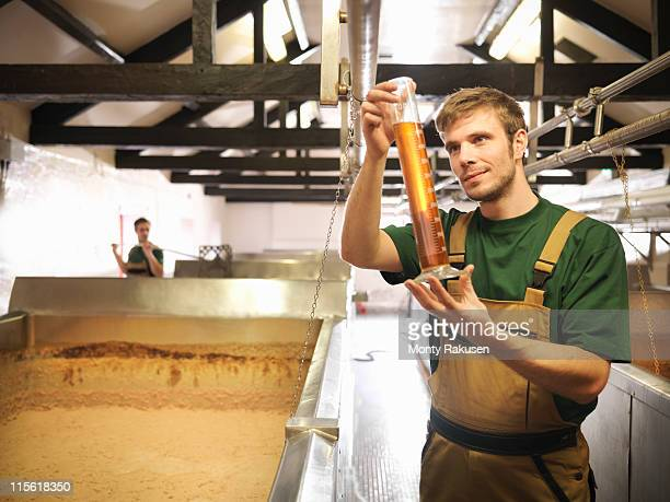 Workers with sample in fermentation room