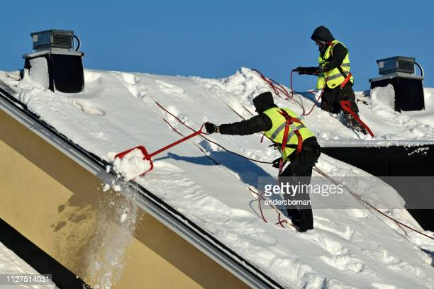 workers with snow shovels carry out winter cleaning of roof of building from snow and ice - absence stock pictures, royalty-free photos & images