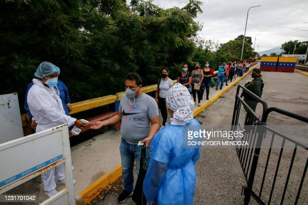 Workers with the Colombian Ministry of Health spray sanitizer on the hands of Venezuelan people lining up to receive food at the Simon Bolivar...