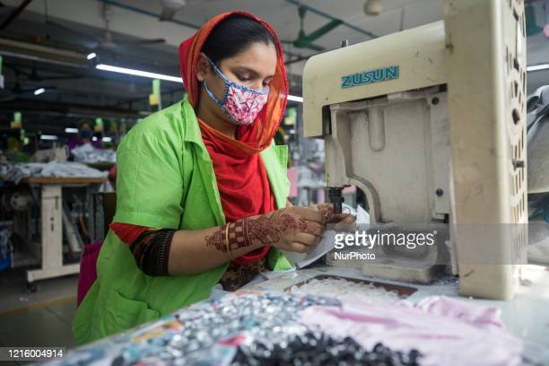 Workers work in a garment factory in Dhaka, Bangladesh on May 28, 2020. Bangladesh workers are returning to factories despite confusion over safety...