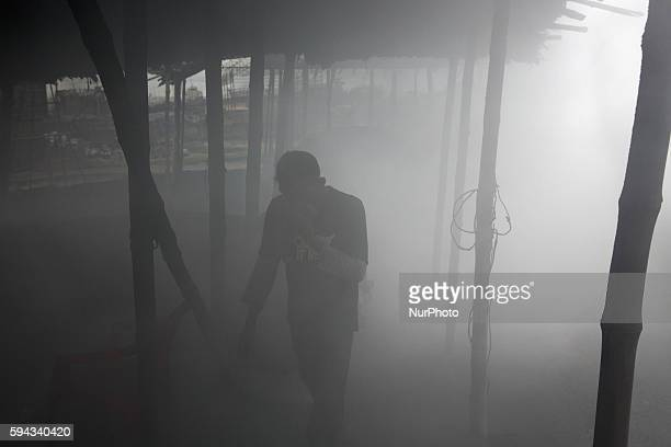 Workers work in factory which is covered with smoke in Dhaka Bangladesh on 22 August 2016 People from the southern part of Bangladesh are the victims...