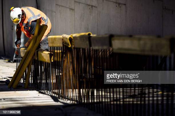 Workers work on a construction site in the heat in The Hague The Netherlands on August 6 2018 as a heatwave sweeps across Europe / Netherlands OUT