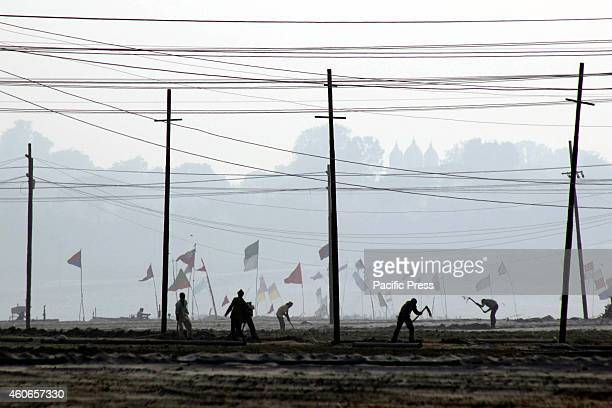 Workers work on a foggy morning before the annual 'Magh Mela' festival in Allahabad The month long festival 'Magh' will start on January 15 2015 with...