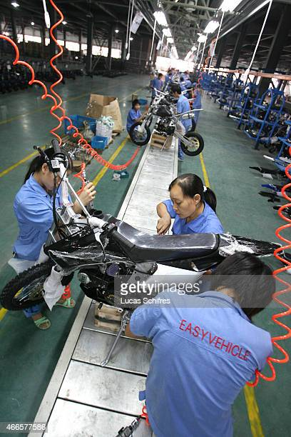 Workers work on an YL306 150 cc dirt bike on the assembly line in Easy vehicle factory on September 17 2007 in Yong Kang Zhejiang province China
