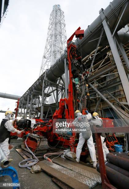 Workers work on the construction of an ice wall at the tsunamicrippled Tokyo Electric Power Co's Fukushima Daiichi Nuclear Power Plant in Okuma...