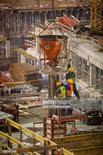Workers work on the construction site of the Polish National stadium in Warsaw at sunset on November 26 2009 Poland and Ukraine cohost the Euro 2012...