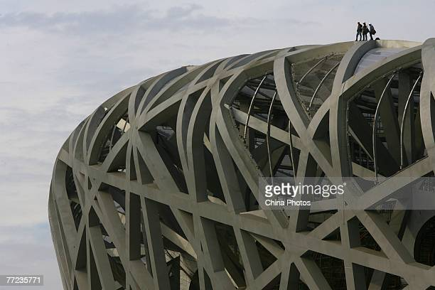 Workers work on the steel structure of the National Stadium dubbed the Bird's Nest on October 9 2007 in Beijing China The main structure of the...
