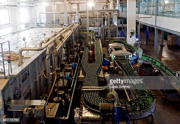 Workers work on the Tsingtao beer production line in Tsingtao brewery on May 17 2009 in the town of Qingdao Shandong province China Tsingtao beer is...