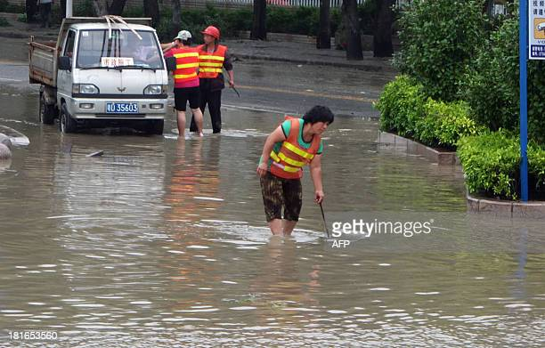 Workers work to drain a flooded street in Shantou south China's Guangdong province on September 23 2013 after Typhoon Usagi landed in...