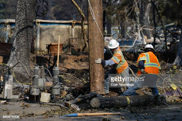 Workers work to repair power lines in the Coffey Park neighborhood following the damage caused by the Tubbs Fire on October 13, 2017 in Santa Rosa,...