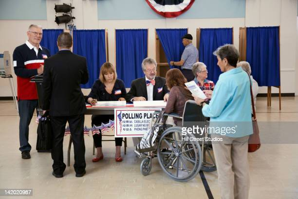 workers working at registration table in polling place - voter registration photos et images de collection