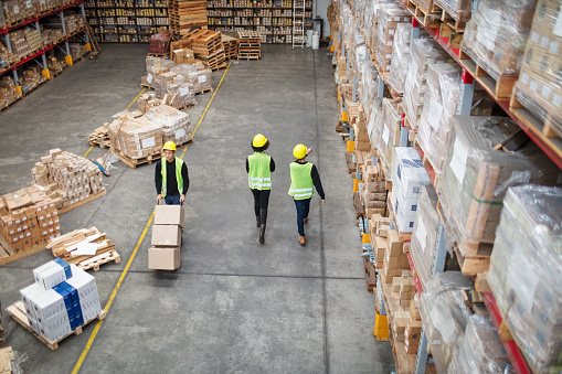 Workers working in large warehouse 1088912402