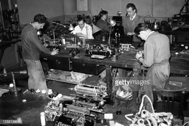 Workers working in the Agence France Presse technical service repair typewriters at the agency's headquarters in Paris in June 1947.