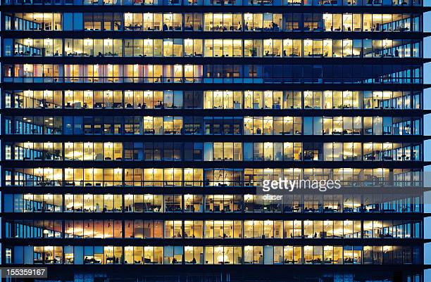 workers working late. office windows by night. - wolkenkrabber stockfoto's en -beelden