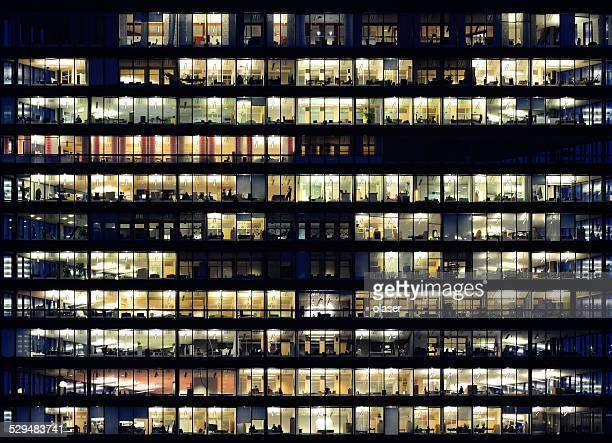workers working late. office windows by night. - night stockfoto's en -beelden