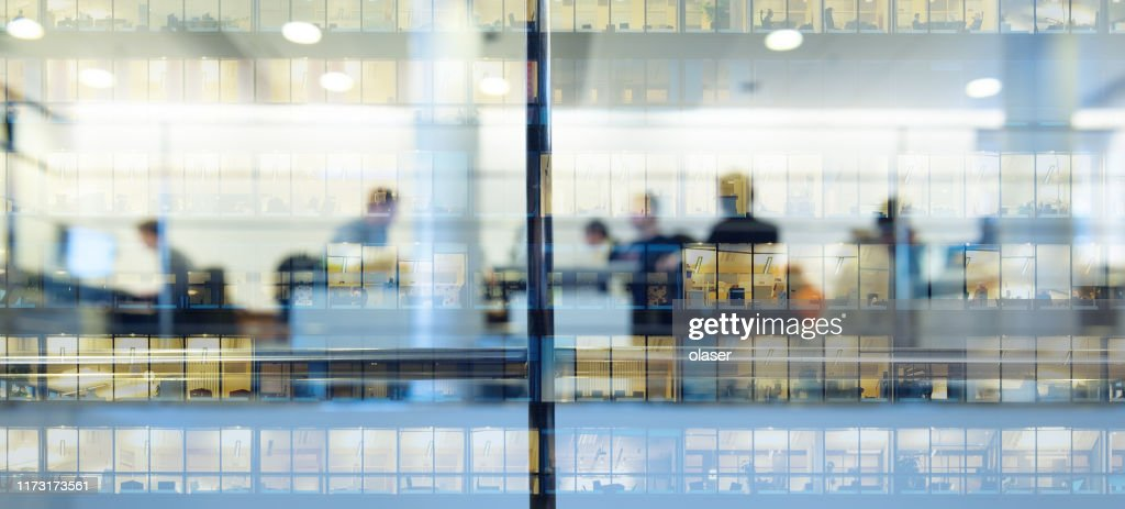 Workers working late. Tall building reflected : Stock Photo