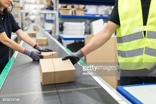 Workers working on conveyor belt in packaging plant