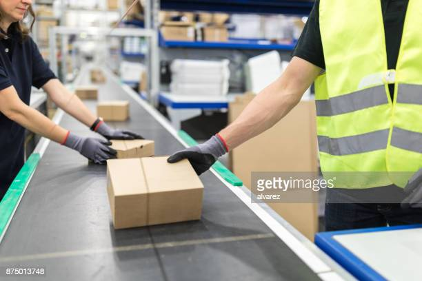workers working on conveyor belt in packaging plant - sending stock photos and pictures