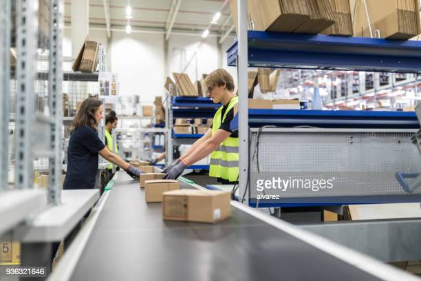 workers working on conveyor belt in warehouse - conveyor belt stock pictures, royalty-free photos & images