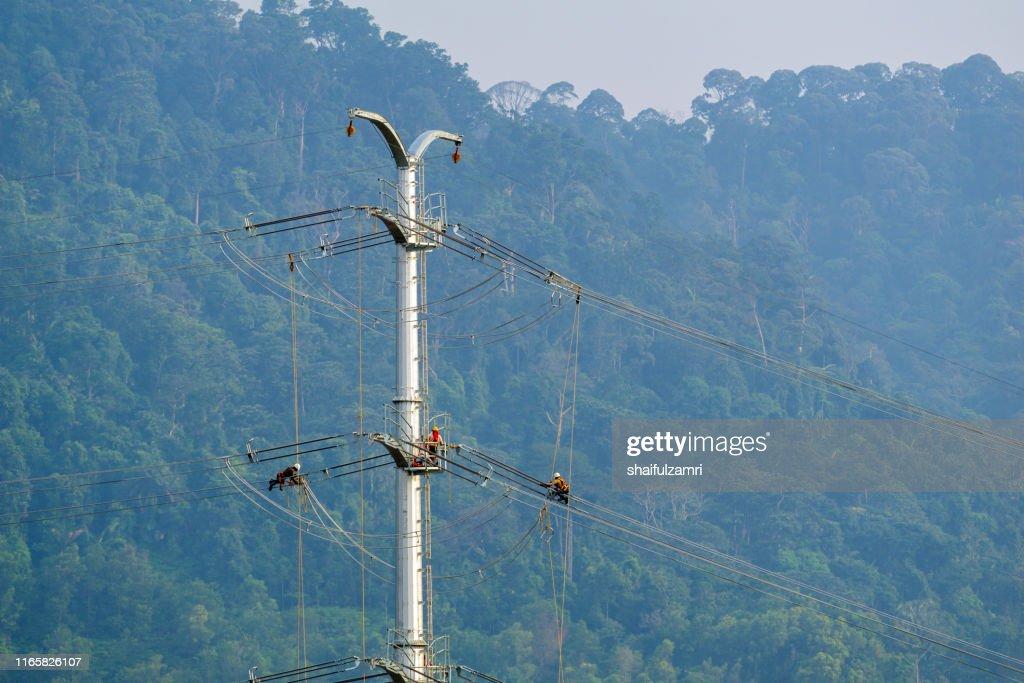 Workers working on power pole at sub urban area of Kuala Lumpur, Malaysia. : Stock Photo