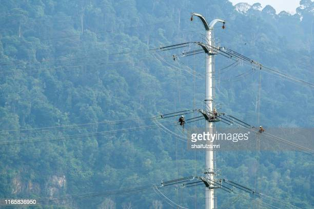 workers working on power pole at sub urban area of kuala lumpur, malaysia. - shaifulzamri stock-fotos und bilder