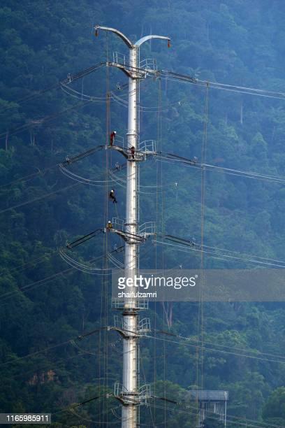 workers working on power pole at sub urban area of kuala lumpur, malaysia. - shaifulzamri - fotografias e filmes do acervo